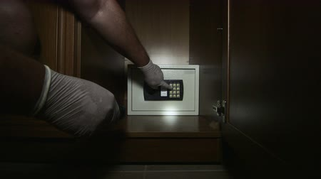 безопасный : Thief trying to open the safe mounted in the closet at home or hotel room Стоковые видеозаписи