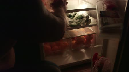 hűtőgép : Man takes out food from the fridge at night Stock mozgókép