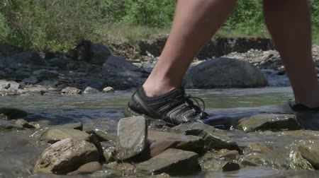 cruzamento : Hikers crossing mountain creek by the ford Stock Footage