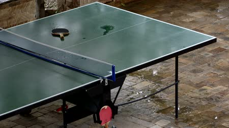 ракетка : Table tennis table in the rain