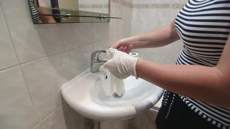 pokojowka : Woman preparing to clean bathroom putting on rubber cleaning gloves