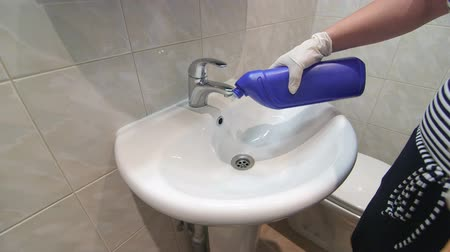 домохозяйка : Housewife cleaning white sink in bathroom with detergent