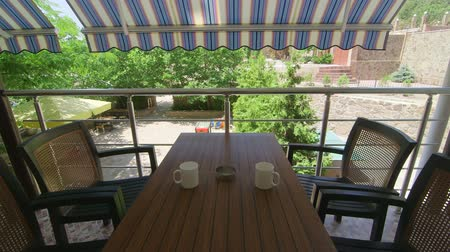 quintal : Table with chairs on the terrace under folding awning in a sunny summer day