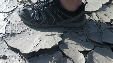 bahno : Slow motion of man in sneakers walking through dried cracked earth