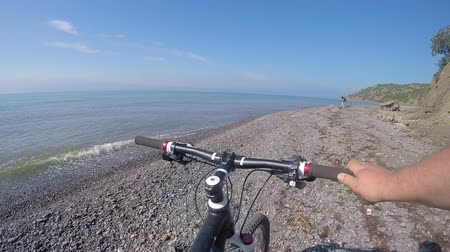 point of view pov : Cyclist Point of view Travelers pushing bikes along the wild pebble beach on the southern sea coast of Crimea