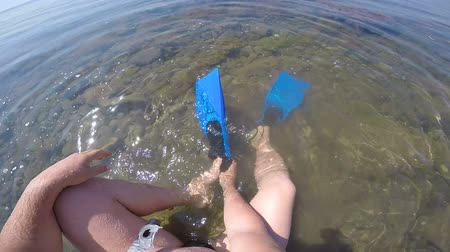 colocando : 1st person POV of diver with snorkeling gear putting on swim fins in the surf Vídeos