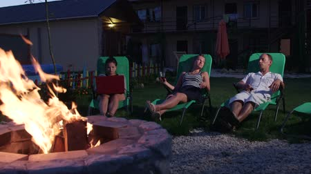 яма : Friends having outdoor garden party with drinks relaxing on lounge chairs near fire pit in evening