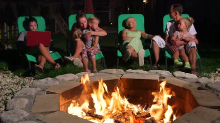 яма : Family with children and friends relaxing near flaming stone patio fire pit outdoor Стоковые видеозаписи