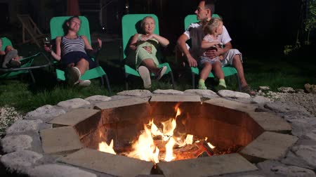 яма : Friends with drinks lying on patio loungers around flaming fire pit talking at twilight