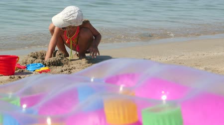 inflável : Cute little girl have fun playing with beach sand toys in surf building sandcastle