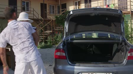 аренда : Family arrival at small resort hotel vacationers unloads luggage from car trunk