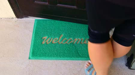 přední : Welcome home mat female traveler with suitcase passes through the front door Dostupné videozáznamy