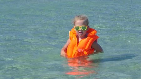inflável : Cute little girl wearing orange life jacket in turquoise water on beach vacation Vídeos