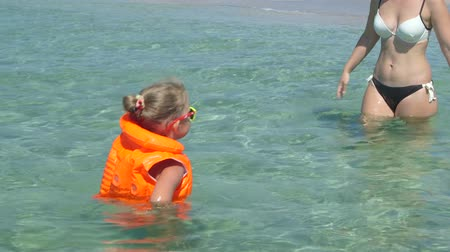 lesson : Young family on beach vacation have fun in water teaching little daughter how to swim