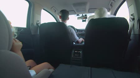 inside car : Young family with little girl in child back seat traveling by car on summer vacation