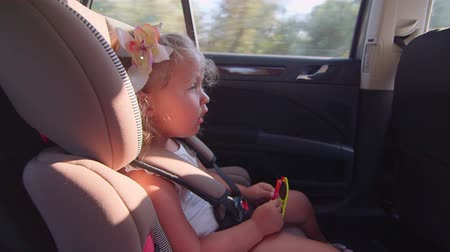 inside car : Pretty little girl sings song sitting in child back seat of car on trip Stock Footage