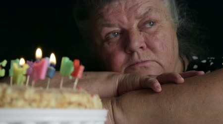 starość : Sad senior woman looking at birthday cake with letter candles happy birthday