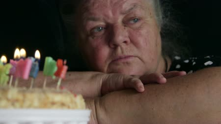 одиноко : Pensive senior woman celebrating alone with birthday cake looking away thinking about something pan shot