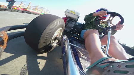 helmets : Karting female driver in helmet rushes go-kart on kart track outdoor POV Stock Footage