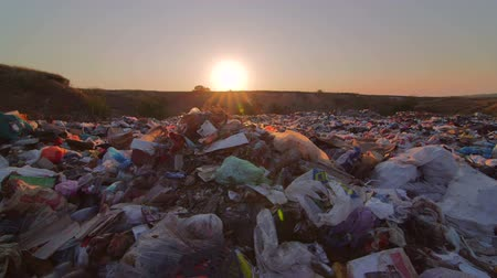 lixo : Sun setting over landfill site of domestic waste pan shot
