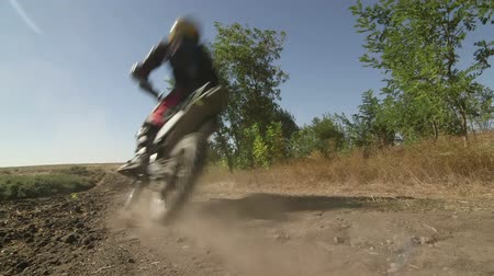 Motocross biker riding enduro motorcycle on dirt track kicking up dust rear view