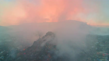 rakás : Burning pile of garbage at dump site toxic smoke rises into the air against setting sun