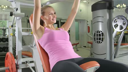 atletika : Young woman lifting too much weight on chest press machine in health fitness club