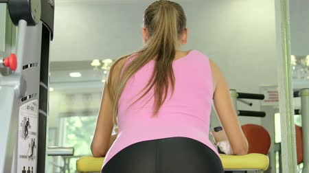 kudrlinky : Woman working out on standing leg curl machine in fitness club closeup rear view