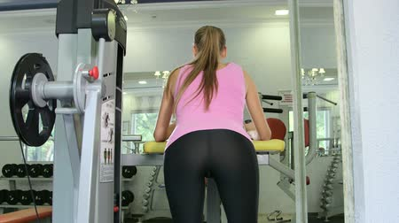 kudrlinky : Fit young woman training in health fitness club on leg curl machine rear view