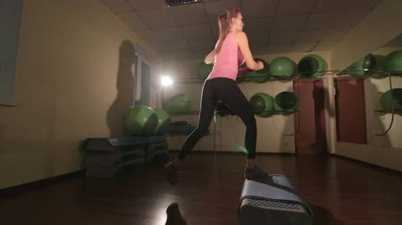 step : JIB CRANE: Fit young woman doing step aerobics exercise in fitness club