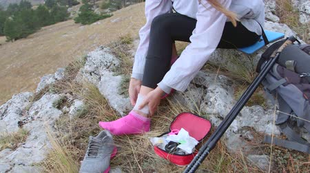 first aid kit : Woman injured while hiking in the mountains wrapping her ankle with bandage using first aid kit Stock Footage