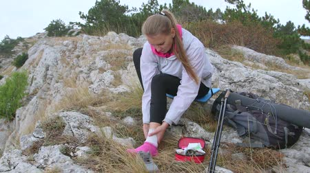 kostka : Young hiking woman sprained ankle using first aid kit applying bandage