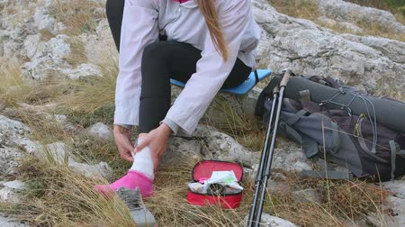 first aid kit : Woman hiker injured while hiking in mountains applying ankle bandage using first aid kit