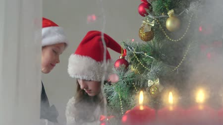 деревья : Children at home decorating Christmas tree view through the window Стоковые видеозаписи