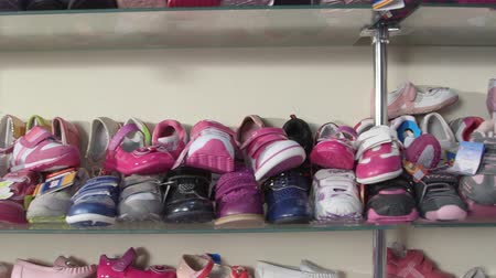 rakás : Rows of shelves piled high with new childrens footwear in the shoe store for sale
