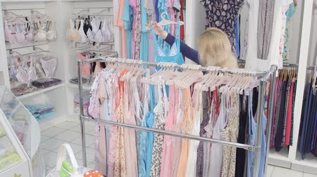 ruházat : Woman buyer looking for clothes in clothing department store Stock mozgókép