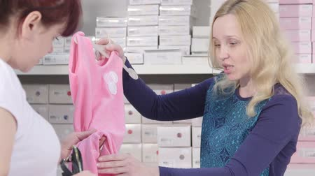 ruházat : Sales assistant showing new infant clothes to female client in baby and maternity shop