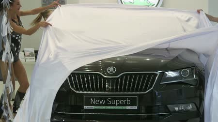 unveil : SIMFEROPOL, RUSSIA - OCTOBER 9, 2015: Spokesmodels unveil the new car Skoda Superb 2015 during presentation in the dealership showroom Avtodom Simferopol