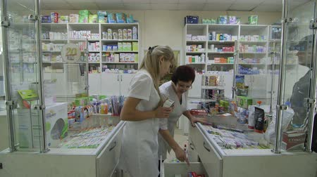 gyógyszeripar : SIMFEROPOL, RUSSIA - CIRCA OCTOBER 2015: Team of pharmacists serving  male customer in russian drugstore pharmacy Stock mozgókép