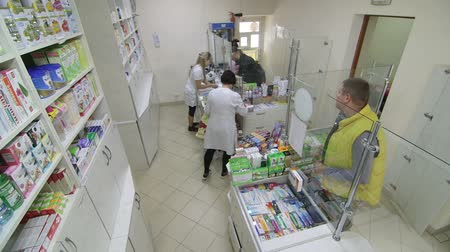 prescrição : SIMFEROPOL, RUSSIA - CIRCA OCTOBER 2015: Team of pharmacists serving customers in pharmacy drugstore, security surveillance camera point of view