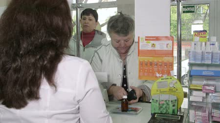купить : SIMFEROPOL, RUSSIA - CIRCA OCTOBER 2015: Senior female customer paying for medicine at russian pharmacy drugstore