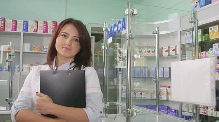gyógyszertár : SIMFEROPOL, RUSSIA - CIRCA OCTOBER 2015: Attractive female pharmacist standing in the pharmacy looking at camera