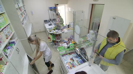 planta de interior : SIMFEROPOL, RUSSIA - CIRCA OCTOBER 2015: Team of pharmacists serving customers in pharmacy drugstore, security surveillance camera point of view