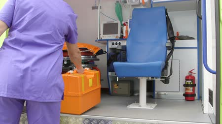 first aid kit : Emergency medical ambulance service female paramedic with life support kit at the site of illness or injury