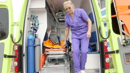 ambulância : Emergency medical service female paramedic taking stretcher out of an ambulance at the site of illness or injury