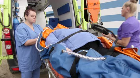 paramedic : Emergency medical ambulance service paramedics crew fixing senior patient on stretcher collapsible vacuum mattress with safety belts Stock Footage