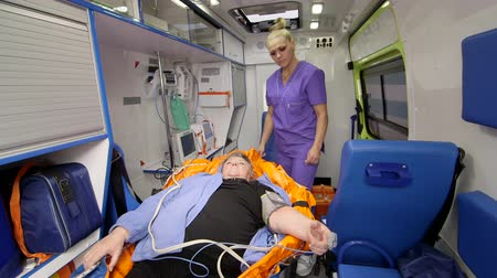pulso : EMT professional provide emergency medical care for senior cardiac patient in ambulance
