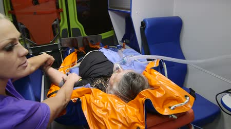 oksijen : Paramedic provide medical care to obese senior patient in emergency ambulance measuring blood pressure Stok Video