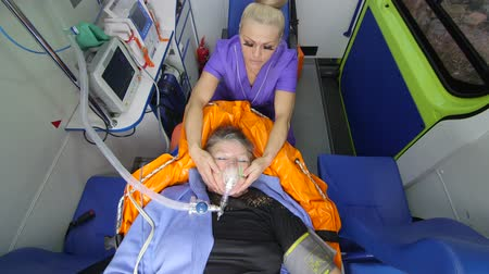 acil durum : Emergency medical service paramedic holding patient head wearing oxygen mask in ambulance monitoring obese senior woman condition during transportation to the nearest hospital
