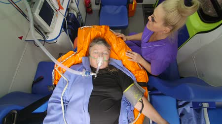 paramedic : Female EMT paramedic provide medical care to critical senior woman patient with eyes closed in ambulance, camera directly above Stock Footage